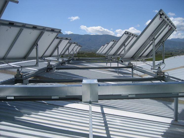 Pannelli con inseguitori solari (solar trackers) installati sul tetto di un capannone