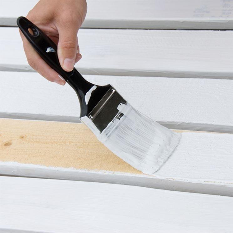 pennello che dipinge sul legno vernice bianca